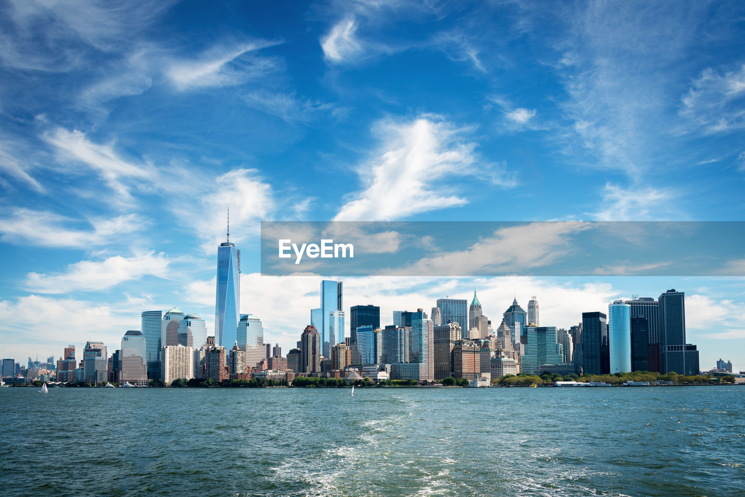 Modern cityscape by river against sky