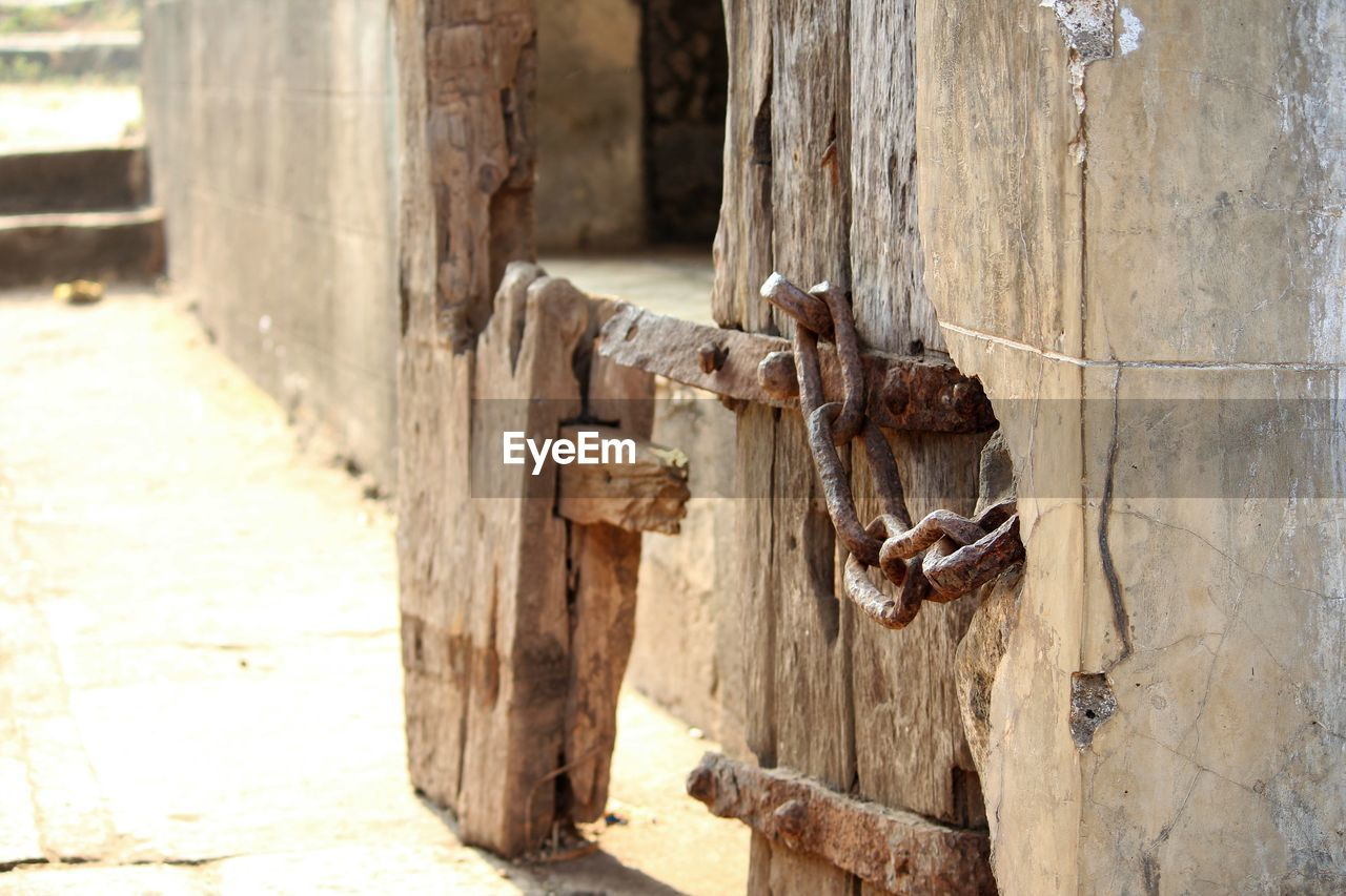 wood - material, no people, day, focus on foreground, close-up, outdoors, door, metal, old, entrance, textured, weathered, sunlight, safety, rusty, protection, wood, nature, nail, security, latch, wooden post