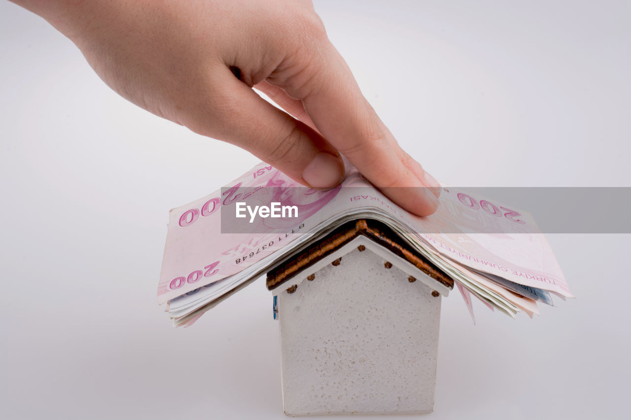 Close-up of hand holding paper currency on model home against white background