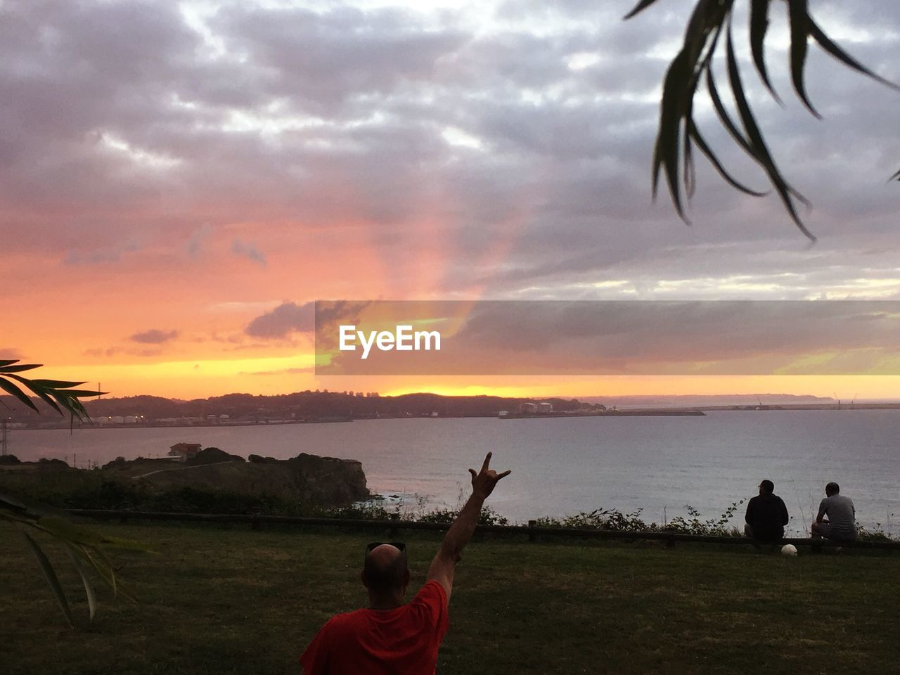 Rear View Of Man Gesturing Horn Sign Against Sea During Sunset