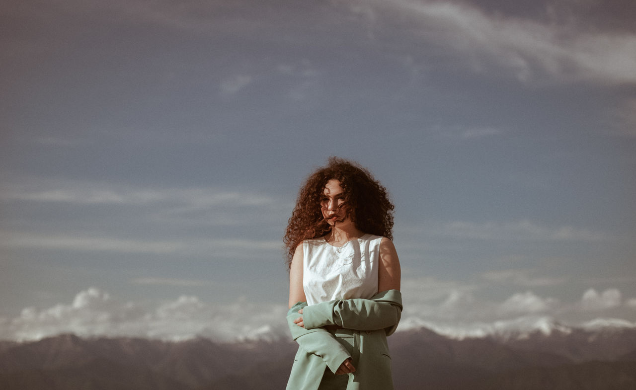 sky, cloud - sky, one person, standing, hairstyle, leisure activity, real people, lifestyles, women, hair, nature, adult, three quarter length, casual clothing, long hair, curly hair, young adult, day, rear view, outdoors, beautiful woman, looking at view