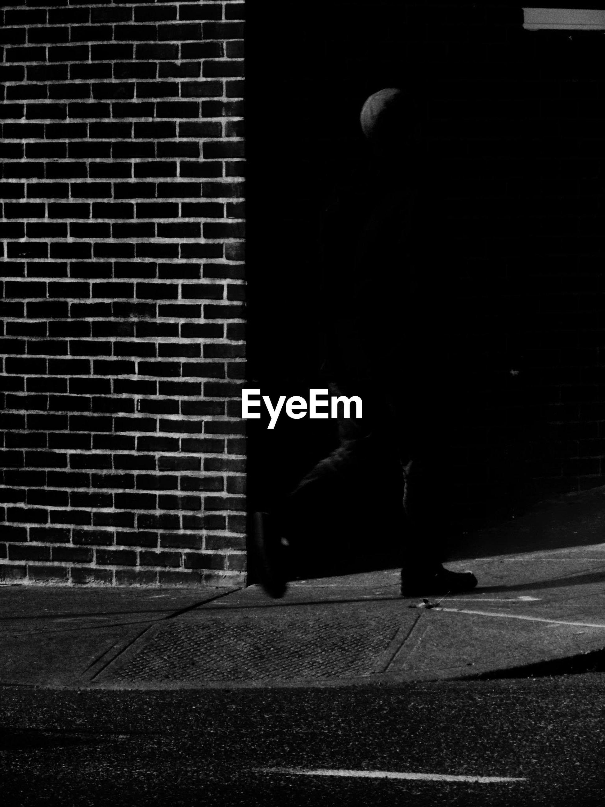 Person walking on sidewalk against brick wall
