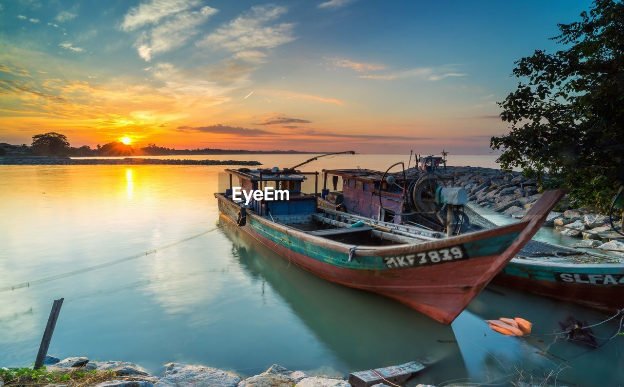 nautical vessel, sky, transportation, sunset, mode of transportation, water, moored, cloud - sky, orange color, tranquility, nature, beauty in nature, tranquil scene, no people, scenics - nature, sun, reflection, outdoors, idyllic, fishing boat, fishing industry, marina