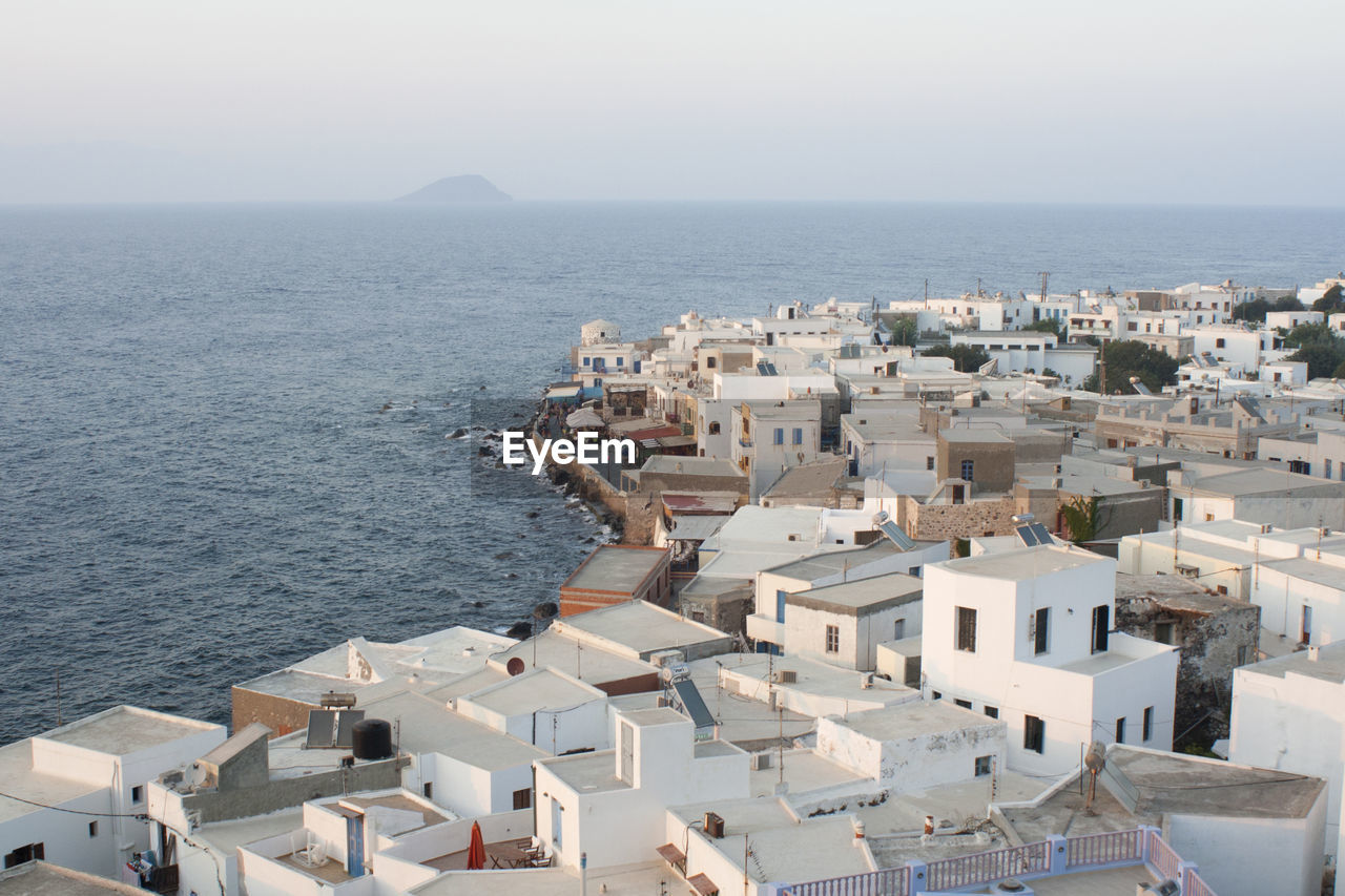 High angle view of town by sea against clear sky