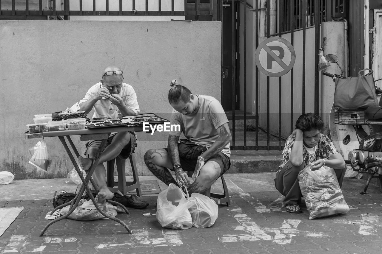 full length, boys, sitting, real people, girls, communication, elementary age, childhood, playing, casual clothing, lifestyles, leisure activity, music, arts culture and entertainment, building exterior, outdoors, togetherness, architecture, men, day, child, city, musician, young adult, people, adult