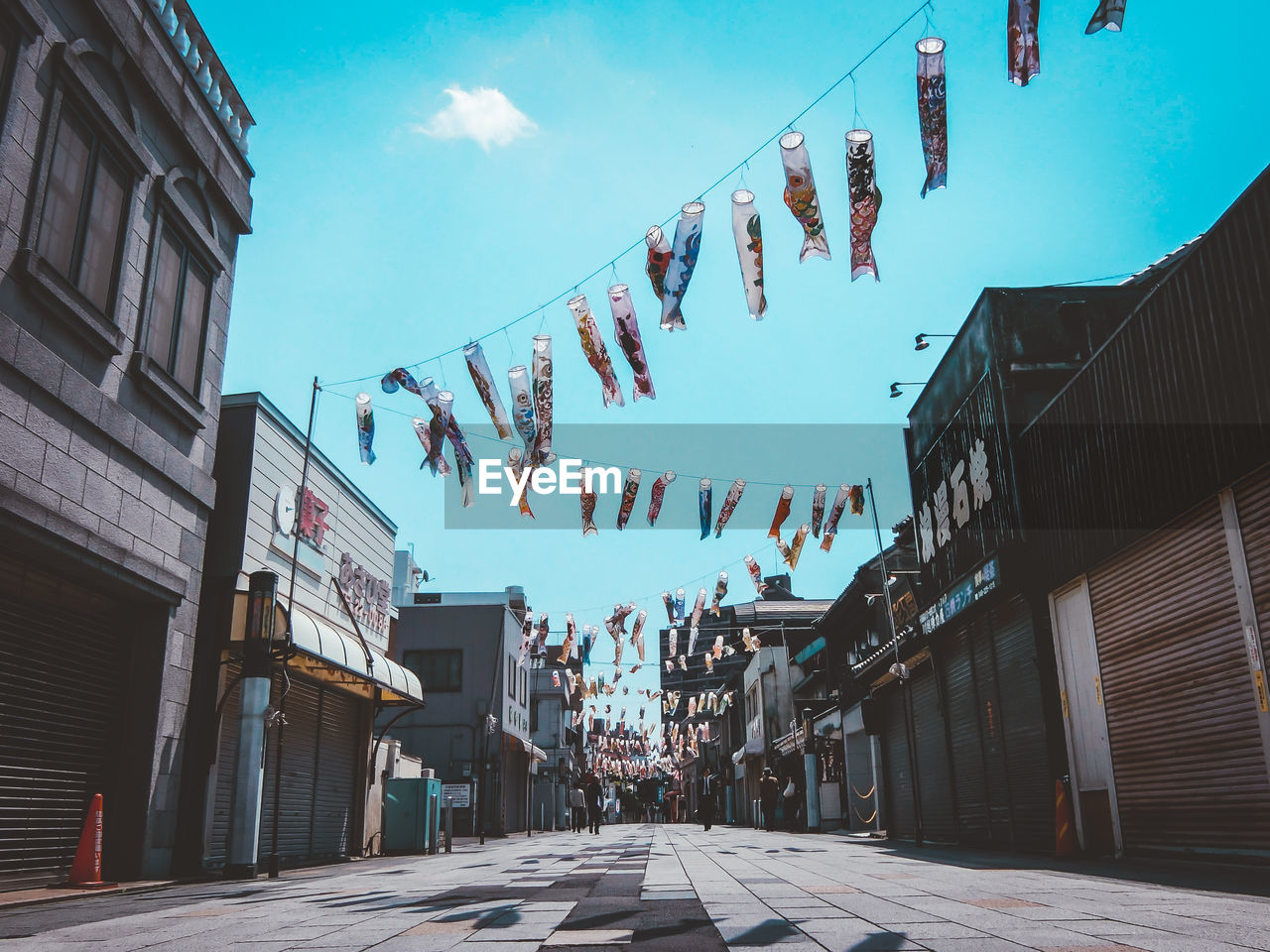 building exterior, built structure, architecture, sky, building, nature, city, day, hanging, no people, cloud - sky, low angle view, direction, outdoors, bunting, text, decoration, street, in a row, residential district
