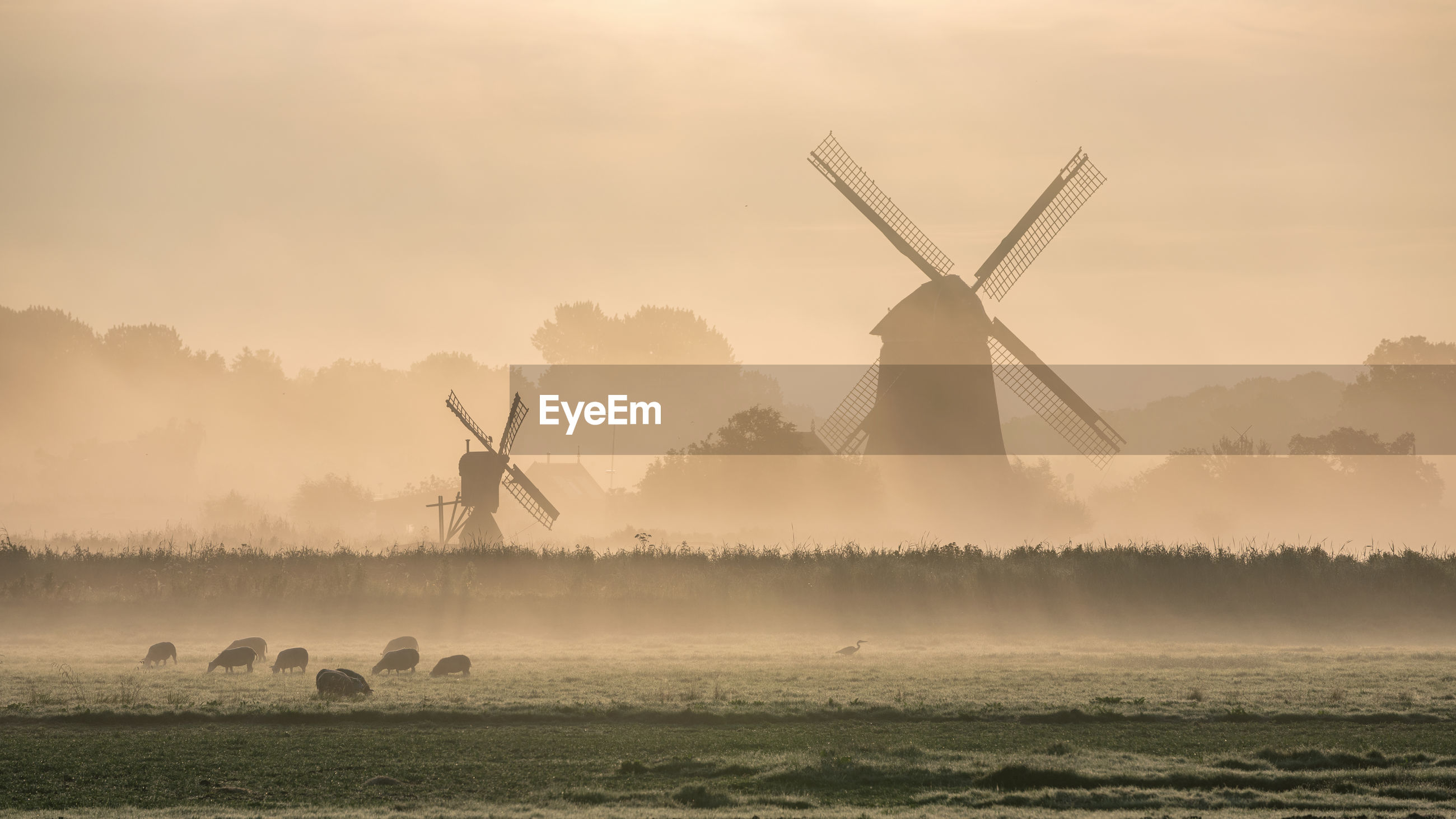 Traditional windmill on field against sky during sunrise