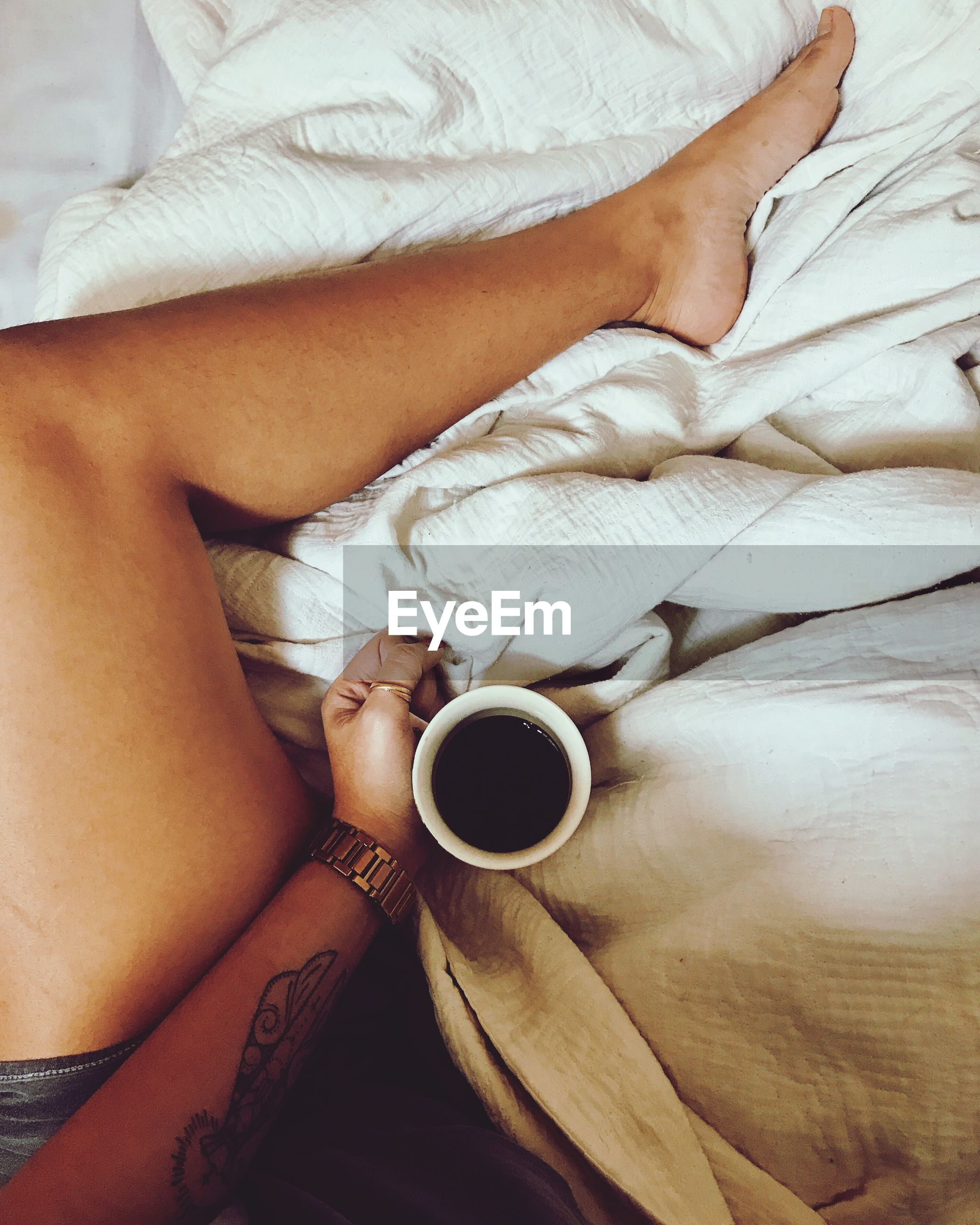 coffee cup, coffee - drink, human hand, bed, human body part, food and drink, one person, drink, cup, indoors, drinking, real people, women, holding, refreshment, bedroom, lifestyles, human leg, relaxation, sheet, tea - hot drink, sitting, men, freshness, close-up, day, adult, people