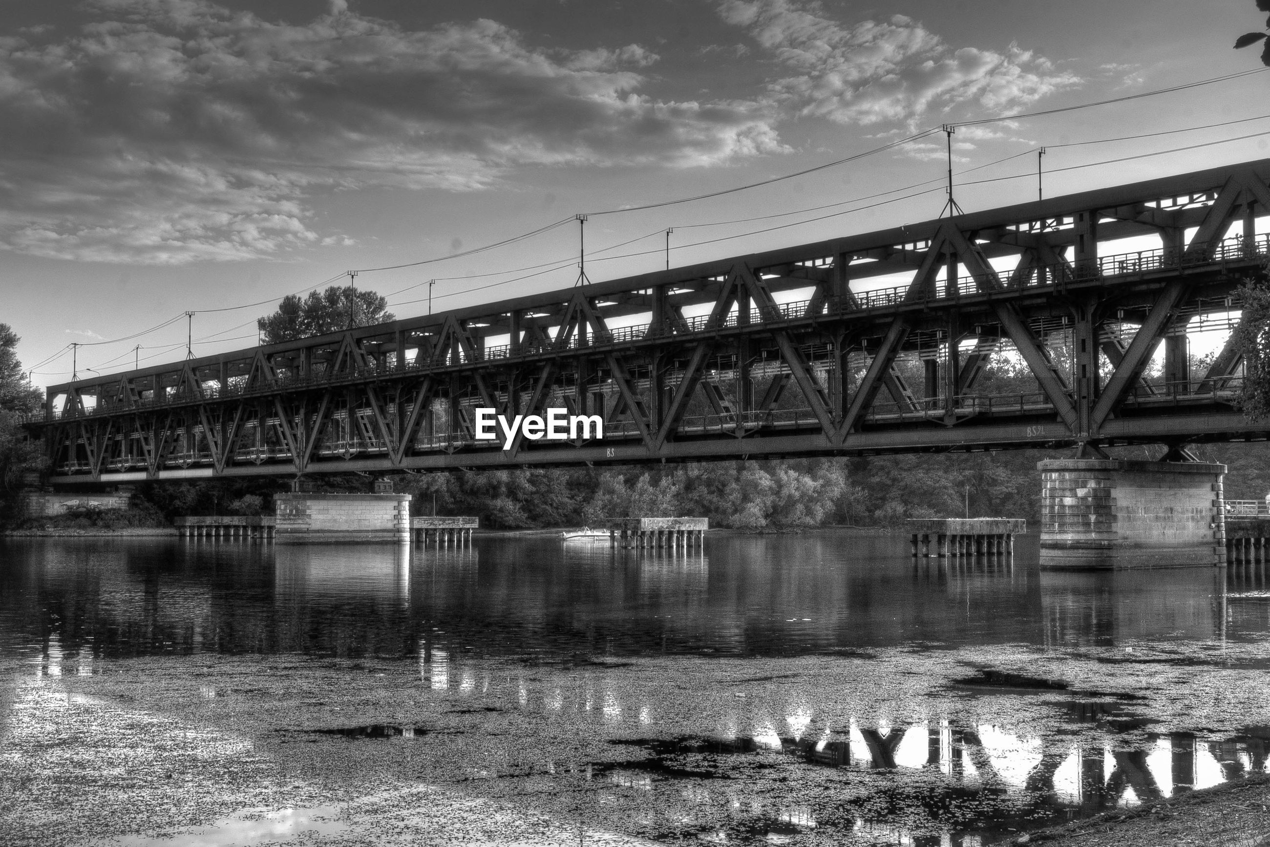 Low angle view of railway bridge over river against sky