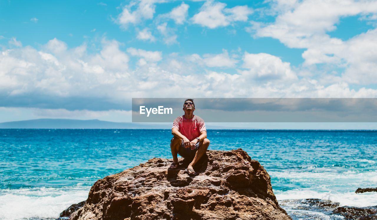 Man sitting on rock against blue sea