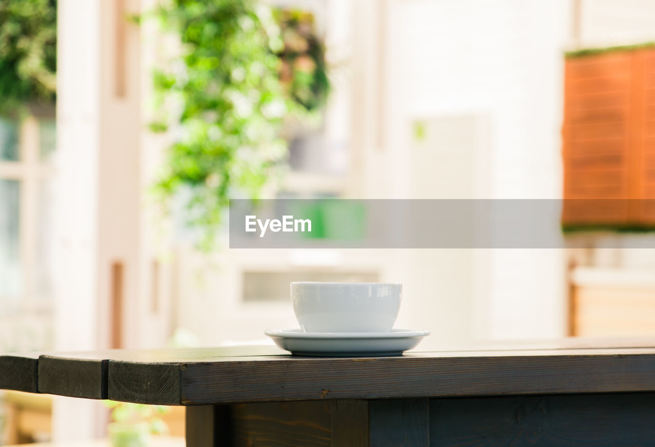 cup, table, mug, food and drink, drink, focus on foreground, coffee cup, indoors, no people, refreshment, saucer, wood - material, coffee, day, coffee - drink, crockery, still life, seat, home interior, close-up, tea cup, non-alcoholic beverage