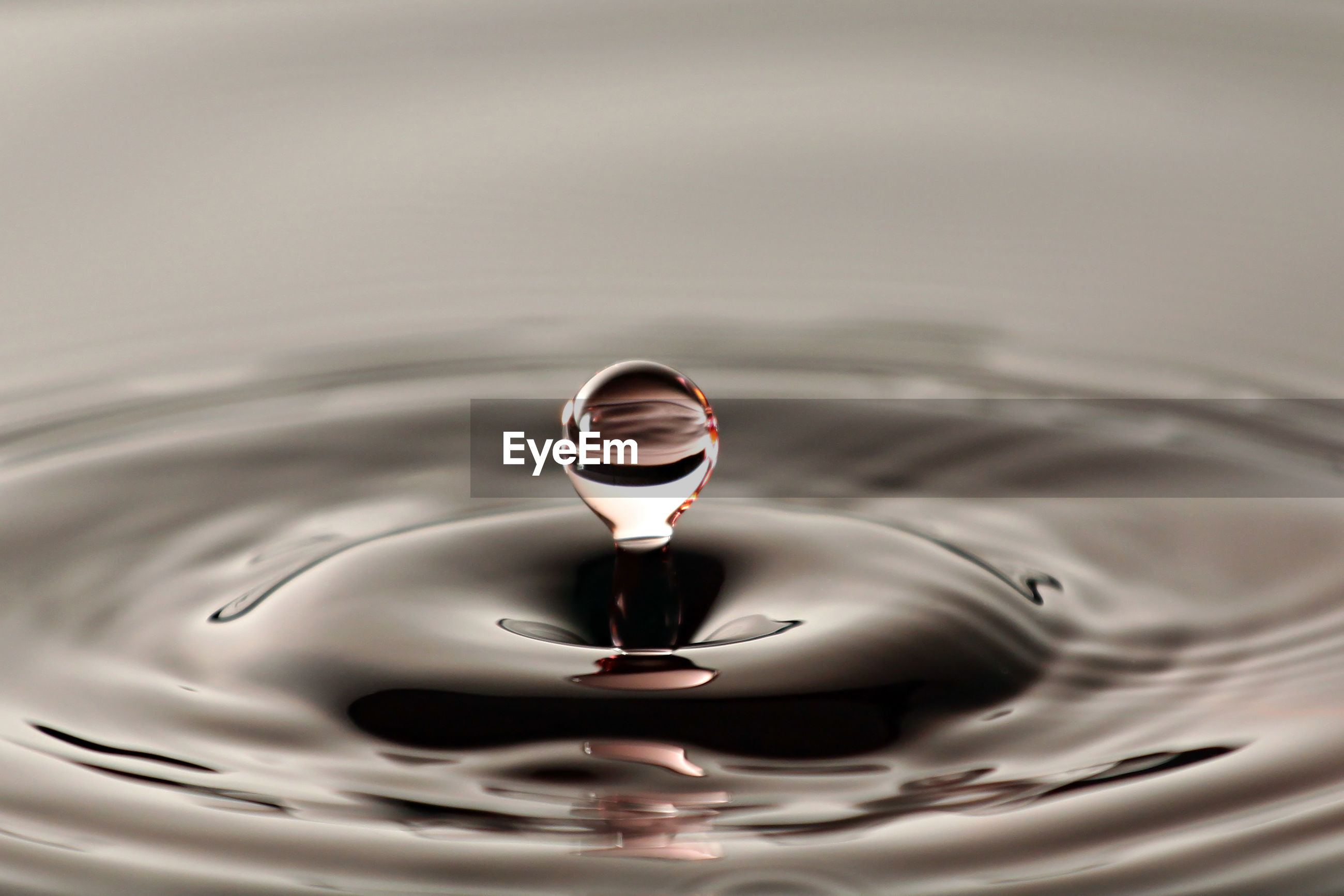 CLOSE-UP OF WATER DROP FALLING ON SURFACE