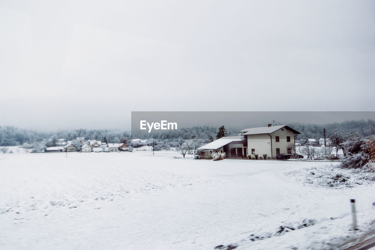 HOUSES ON SNOW COVERED FIELD BY BUILDINGS AGAINST SKY