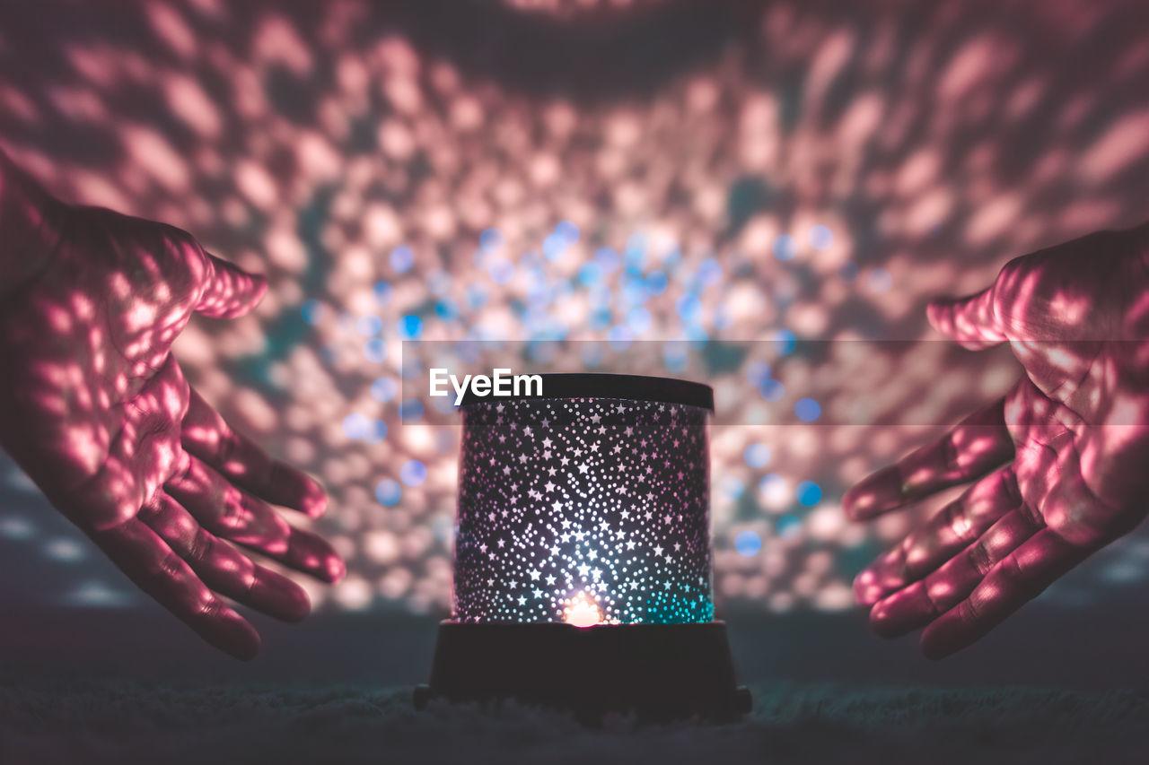 Close-Up Of Hands Around Illuminated Lantern