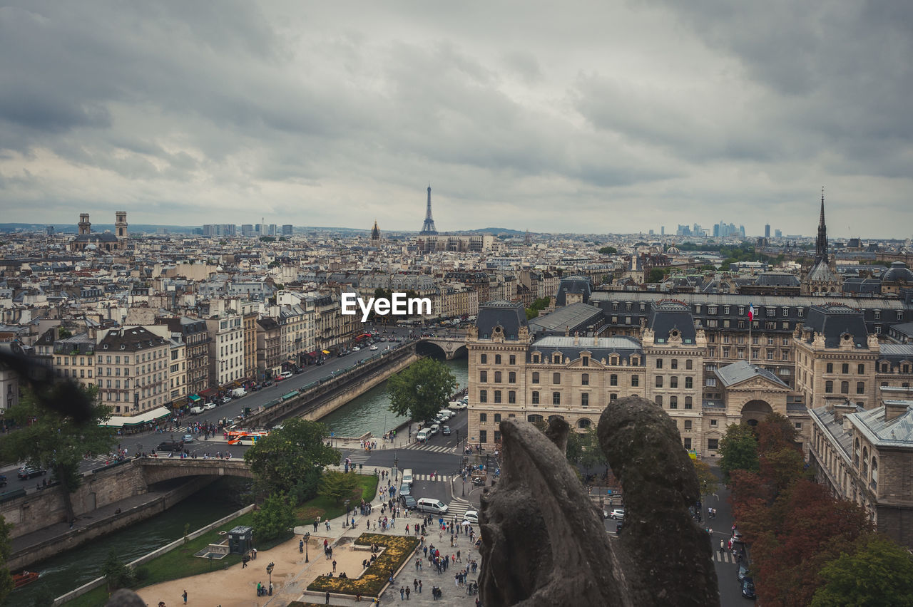Distant view of eiffel tower in city against cloudy sky