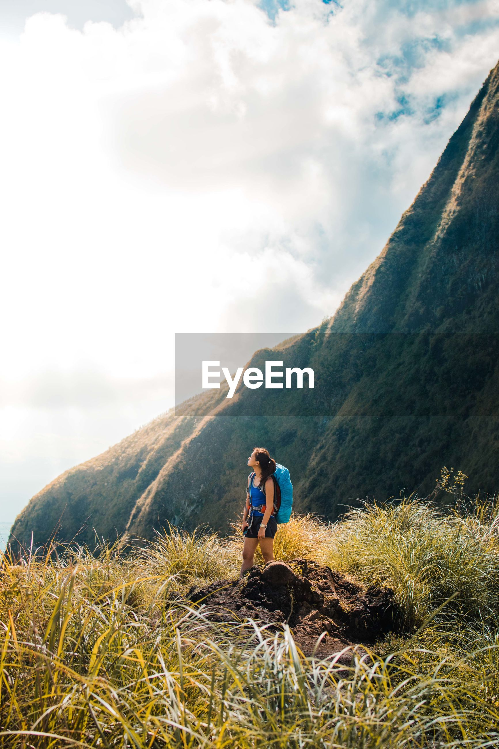WOMAN STANDING ON GRASS AGAINST MOUNTAIN RANGE