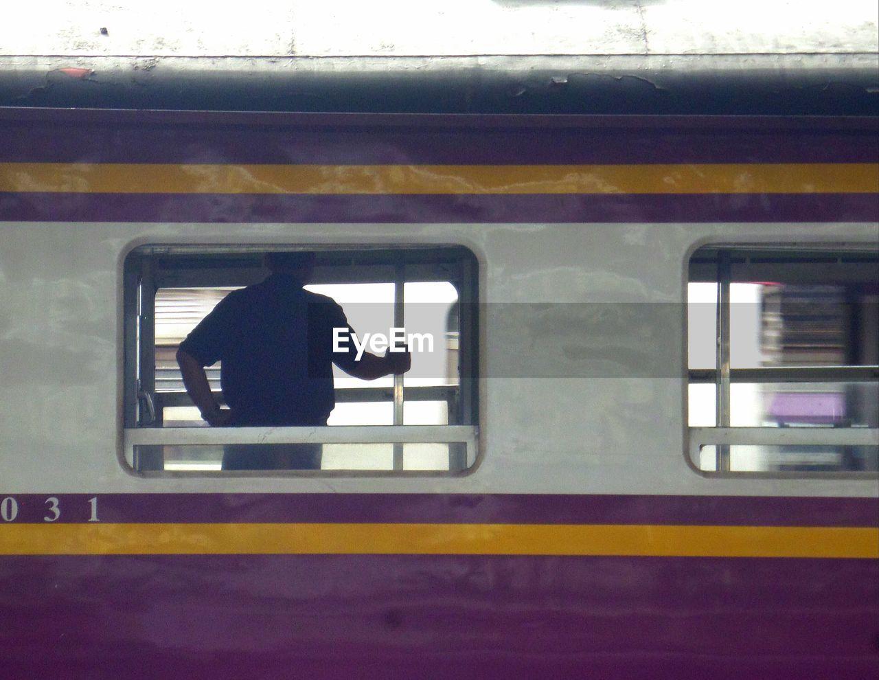 MAN AND TRAIN AT RAILROAD STATION