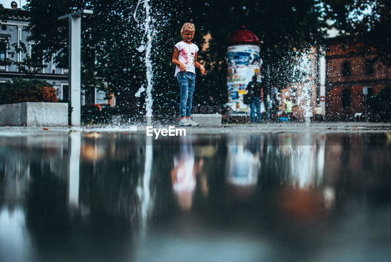 water, real people, leisure activity, one person, full length, casual clothing, lifestyles, motion, fun, young women, young adult, playing, outdoors, day, women, tree, nature, people
