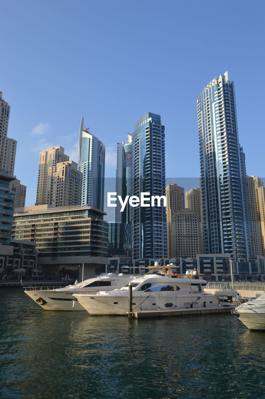 building exterior, architecture, city, nautical vessel, built structure, water, sky, mode of transportation, transportation, office building exterior, building, waterfront, skyscraper, tall - high, modern, cityscape, urban skyline, landscape, nature, no people, yacht, outdoors, luxury, financial district, passenger craft