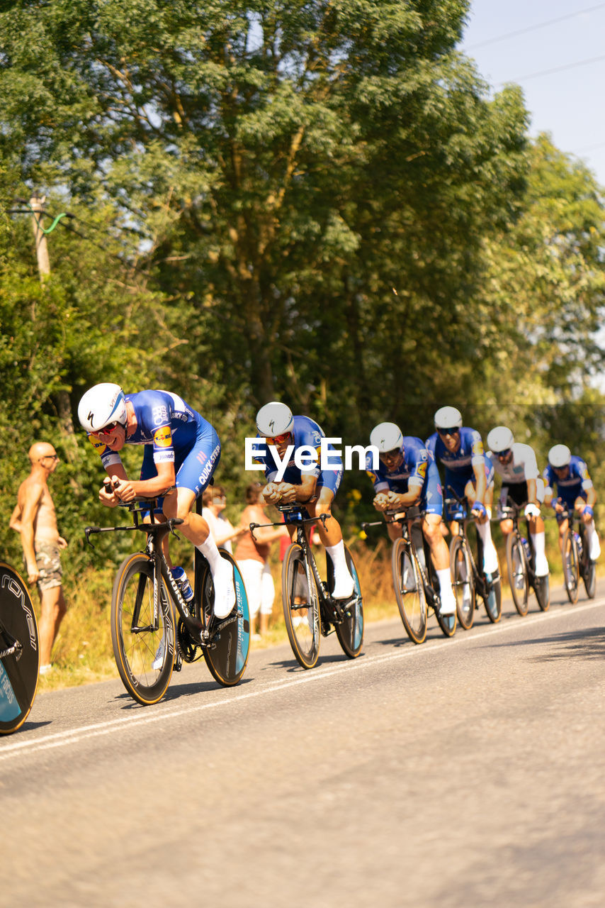 group of people, sport, transportation, competition, bicycle, riding, helmet, ride, activity, headwear, sports race, lifestyles, athlete, men, tree, cycling, motion, people, day, plant, outdoors