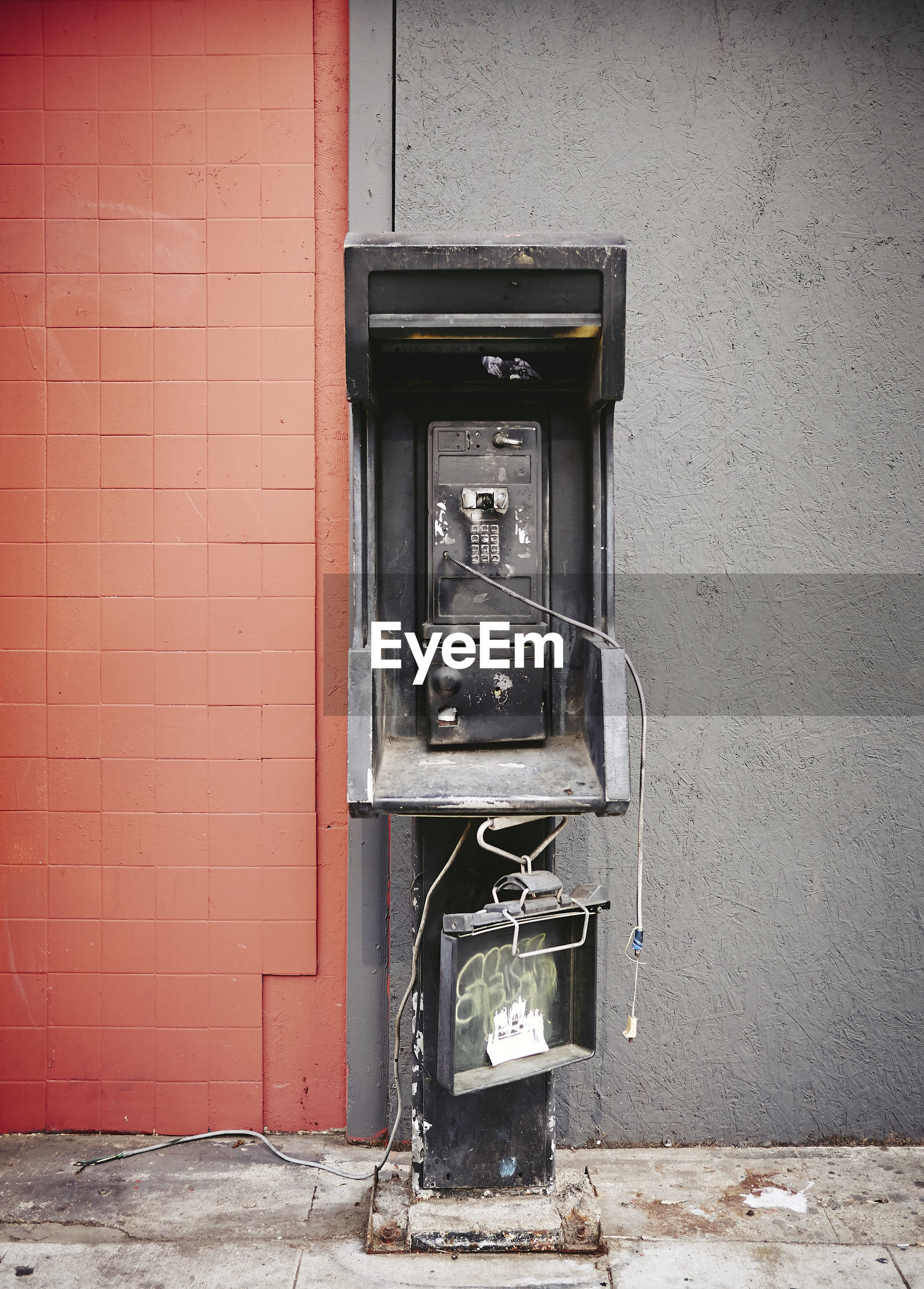 Abandoned telephone booth against wall