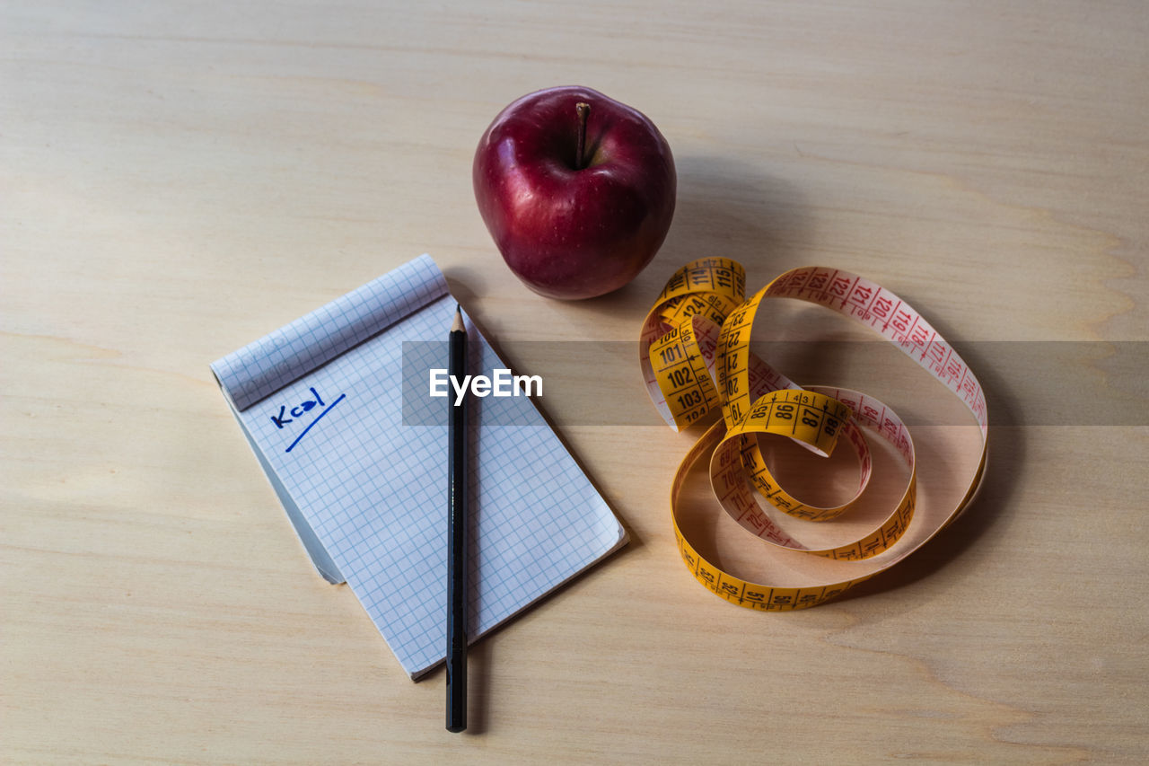 table, indoors, food and drink, food, still life, apple - fruit, high angle view, fruit, book, publication, no people, education, wood - material, freshness, healthy eating, directly above, paper, text, wellbeing, learning