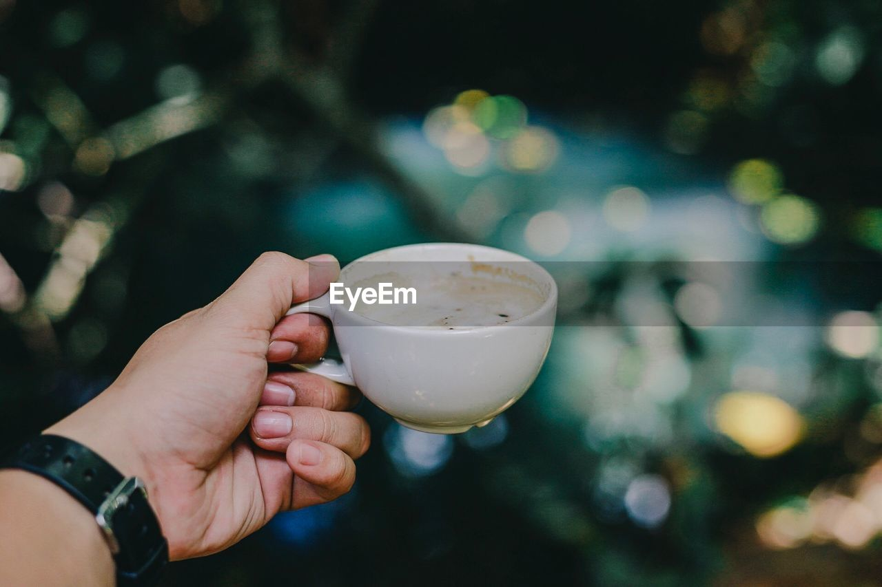 Cropped Image Of Man Hand Holding Coffee Cup Outdoors