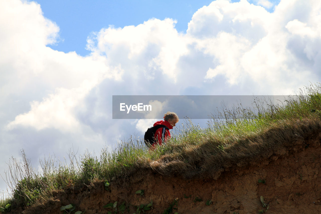 cloud - sky, sky, day, one person, full length, outdoors, field, nature, grass, low angle view, growth, childhood, real people, people
