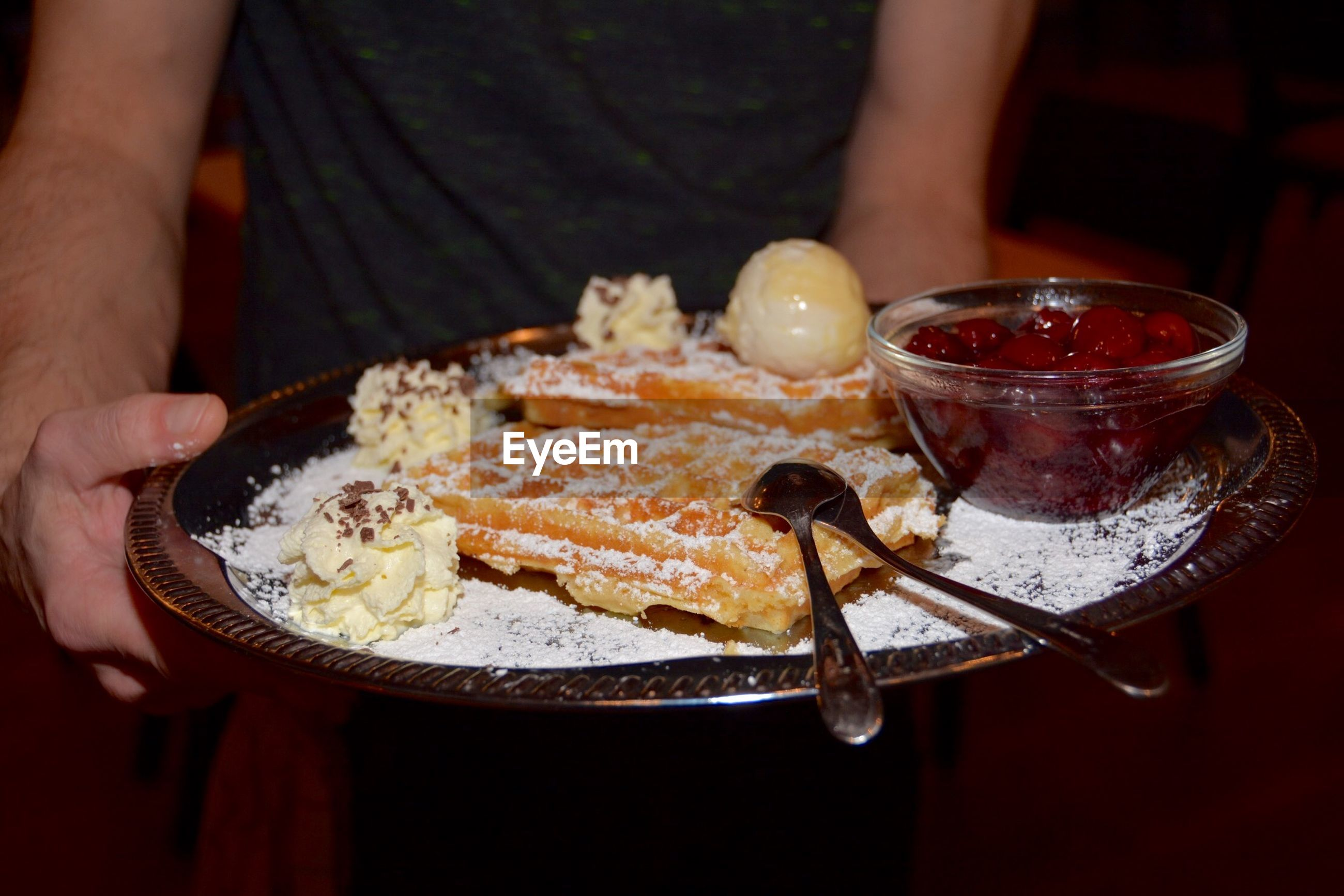 Midsection of man holding waffle with ice cream and cranberry sauce in plate