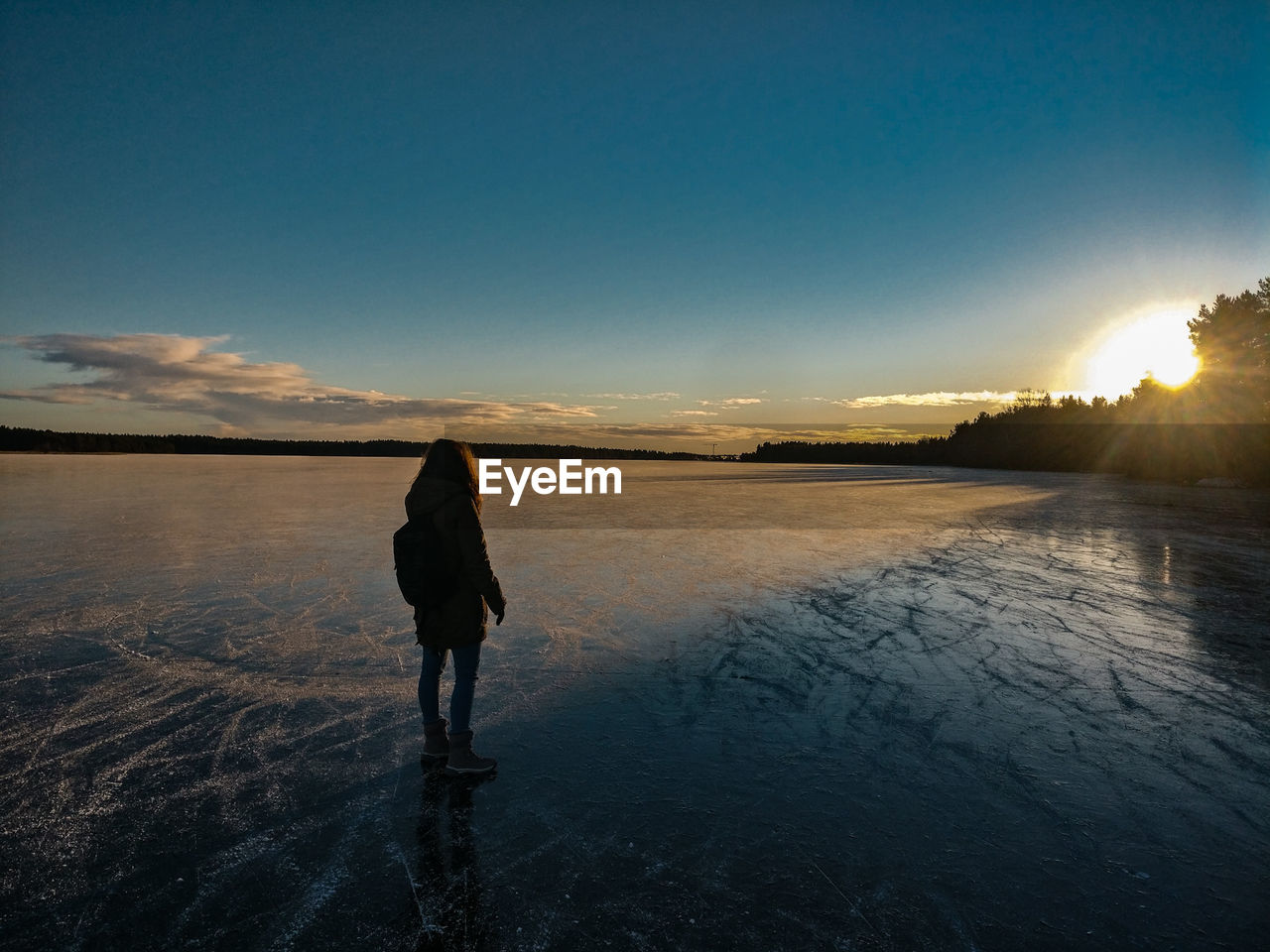 sky, real people, one person, full length, sunset, beauty in nature, rear view, water, lifestyles, nature, leisure activity, scenics - nature, tranquility, tranquil scene, standing, land, non-urban scene, silhouette, outdoors