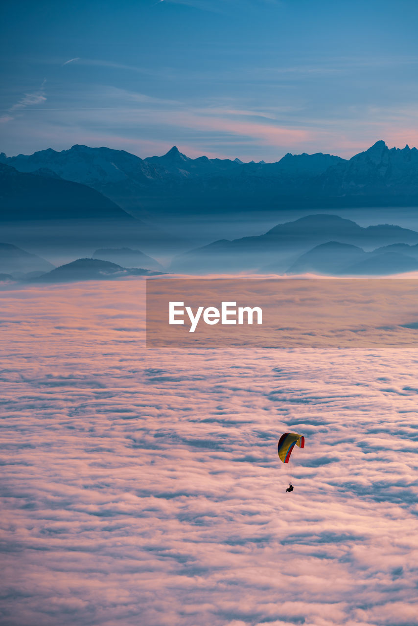 Silhouette of person paragliding over cloudscape