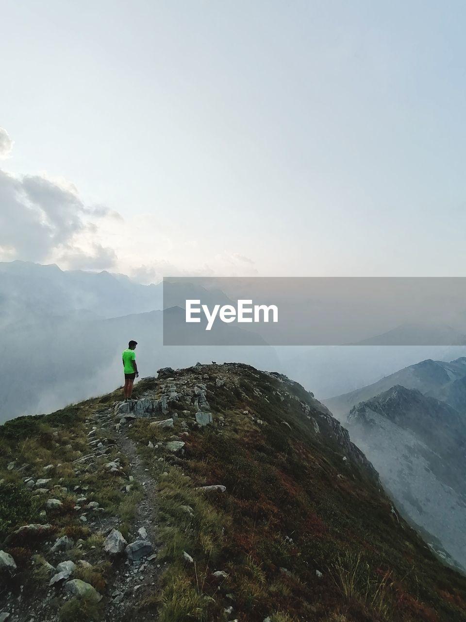 MAN ON ROCKS AGAINST MOUNTAIN RANGE AGAINST SKY