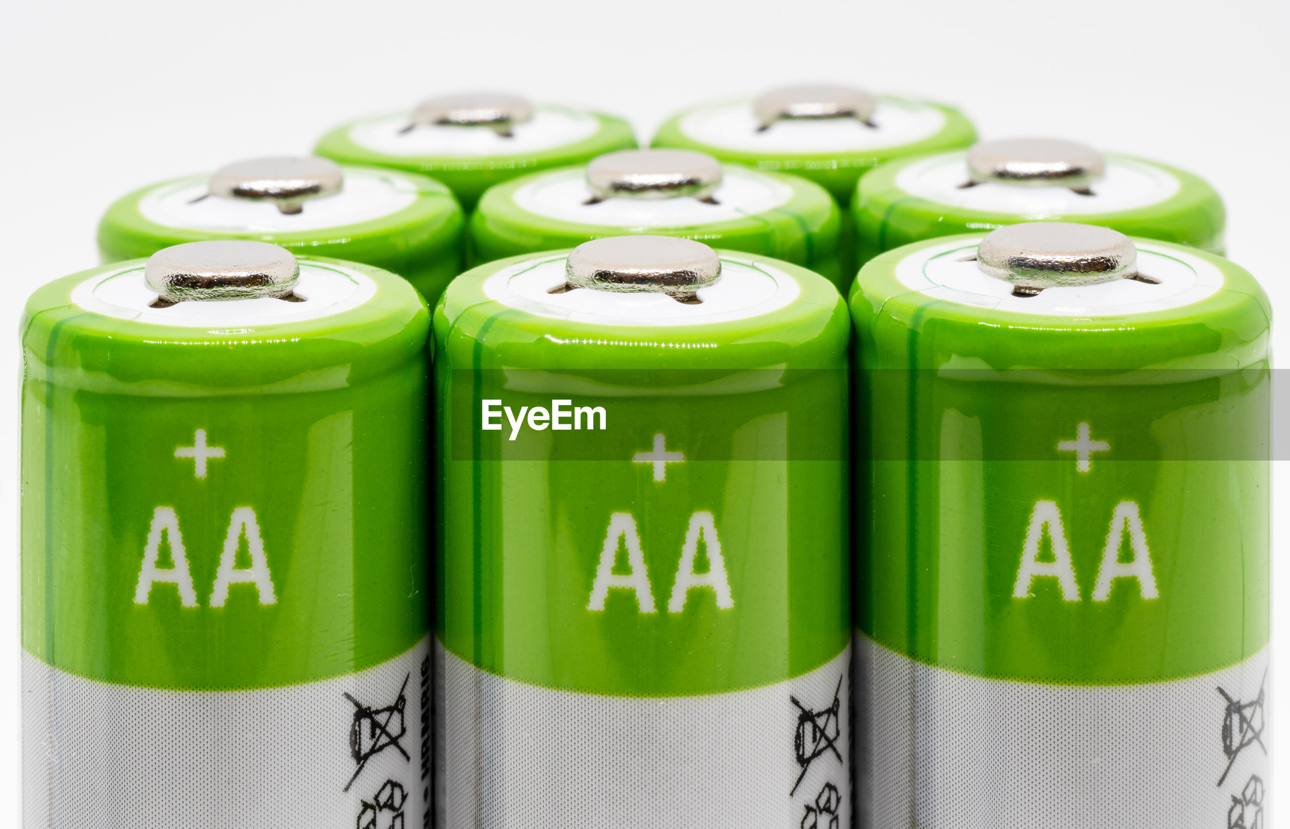 Close-up of green batteries over white background