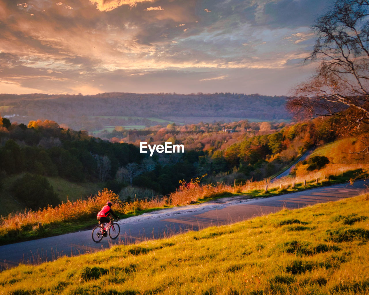 MAN RIDING BICYCLE ON MOUNTAIN ROAD AGAINST SKY