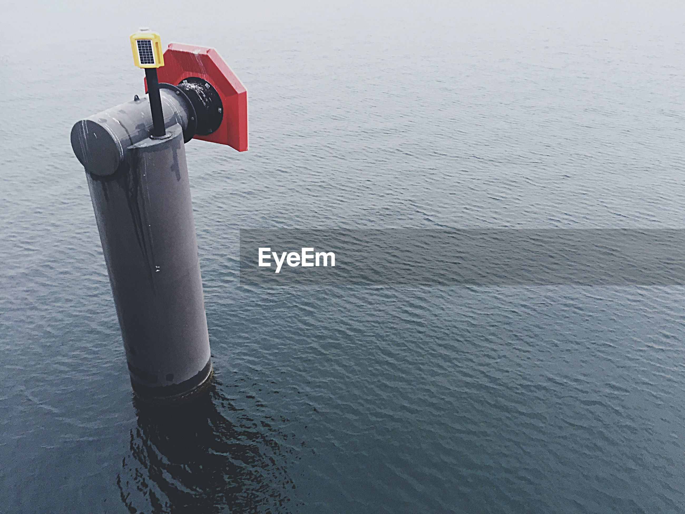 Close-up of pole in calm rippled water