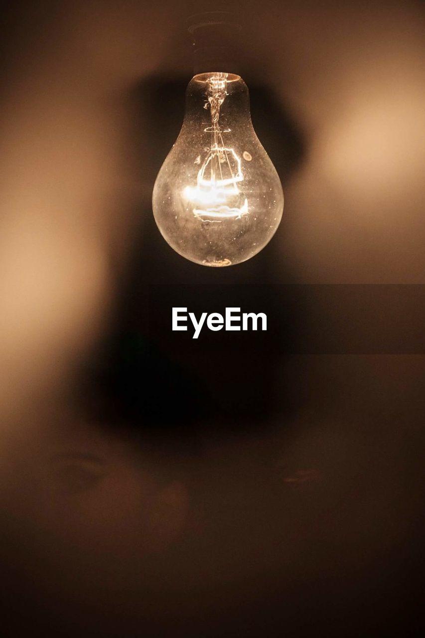 Illuminated light bulb hanging in darkroom