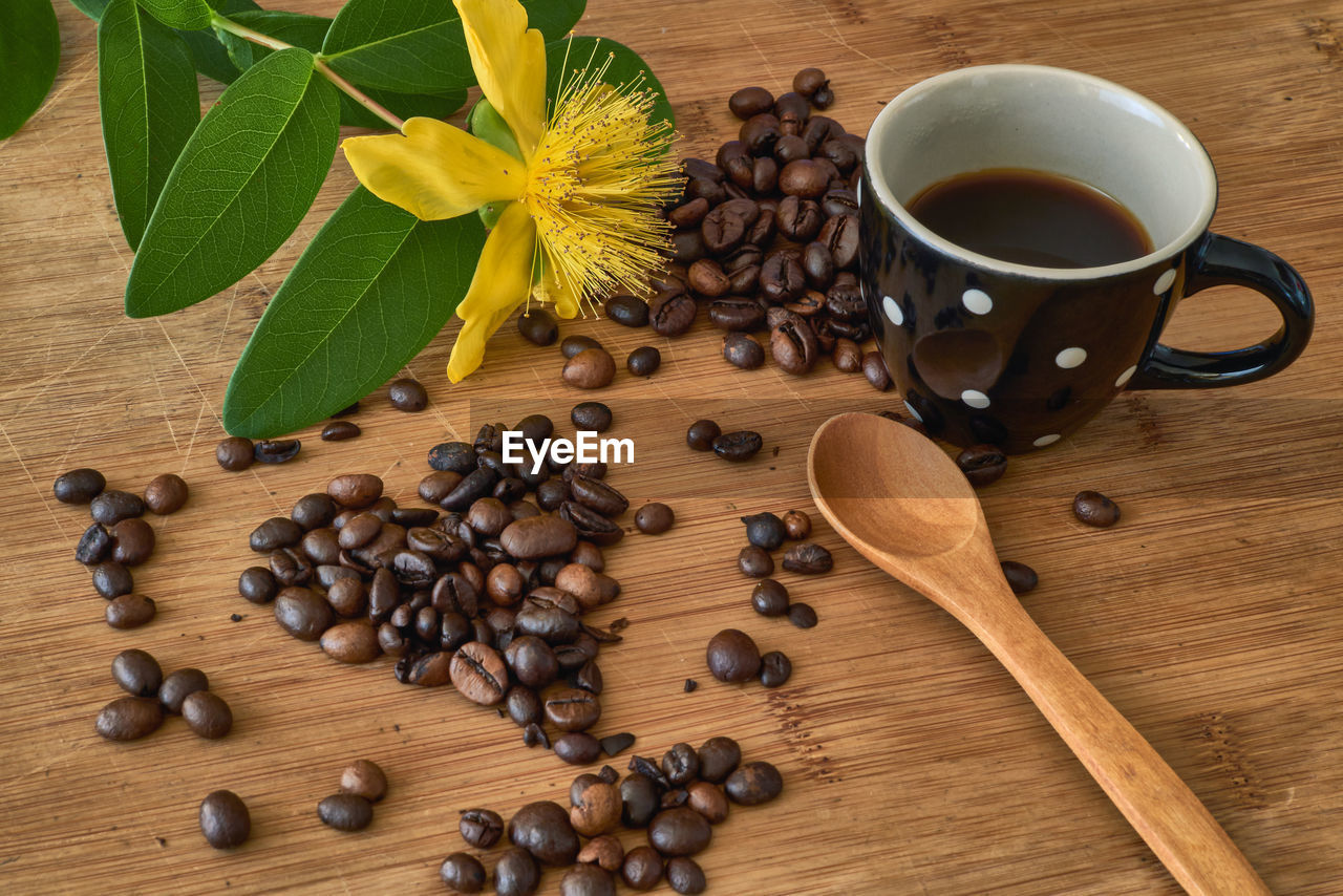 HIGH ANGLE VIEW OF COFFEE BEANS ON TABLE AND LEAVES