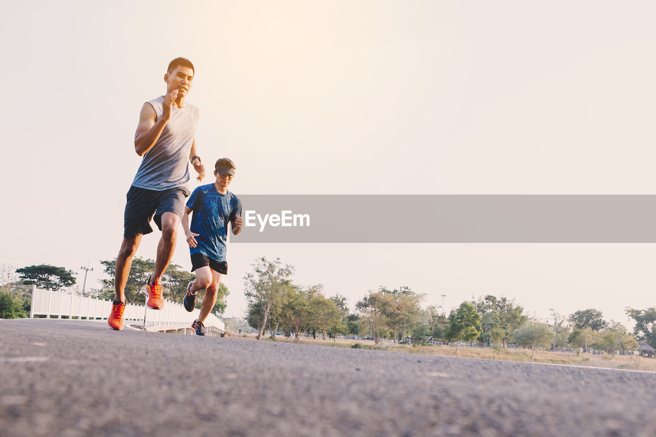 togetherness, men, running, full length, males, lifestyles, road, sky, real people, bonding, child, sport, casual clothing, leisure activity, boys, nature, copy space, day, childhood, transportation, outdoors, positive emotion, son