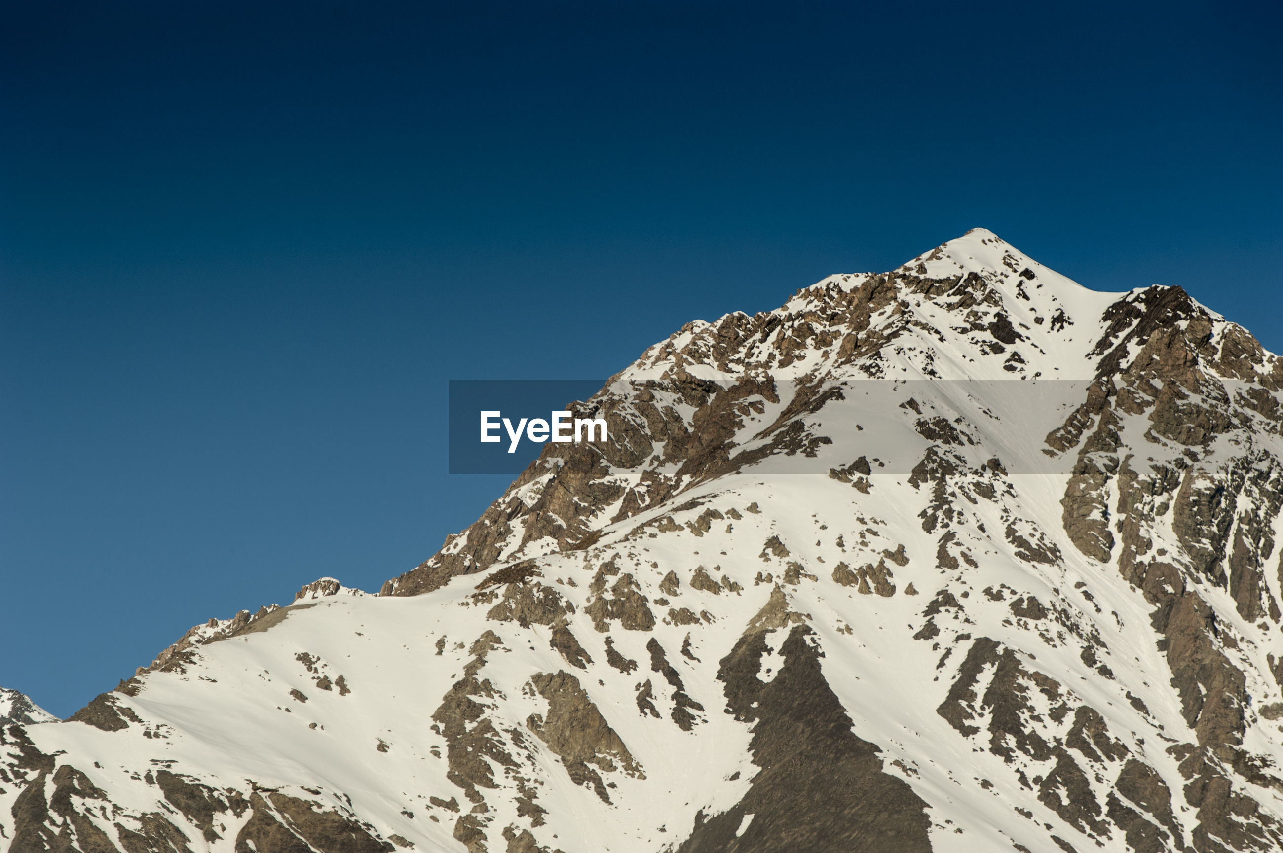 LOW ANGLE VIEW OF SNOWCAPPED MOUNTAIN AGAINST BLUE SKY