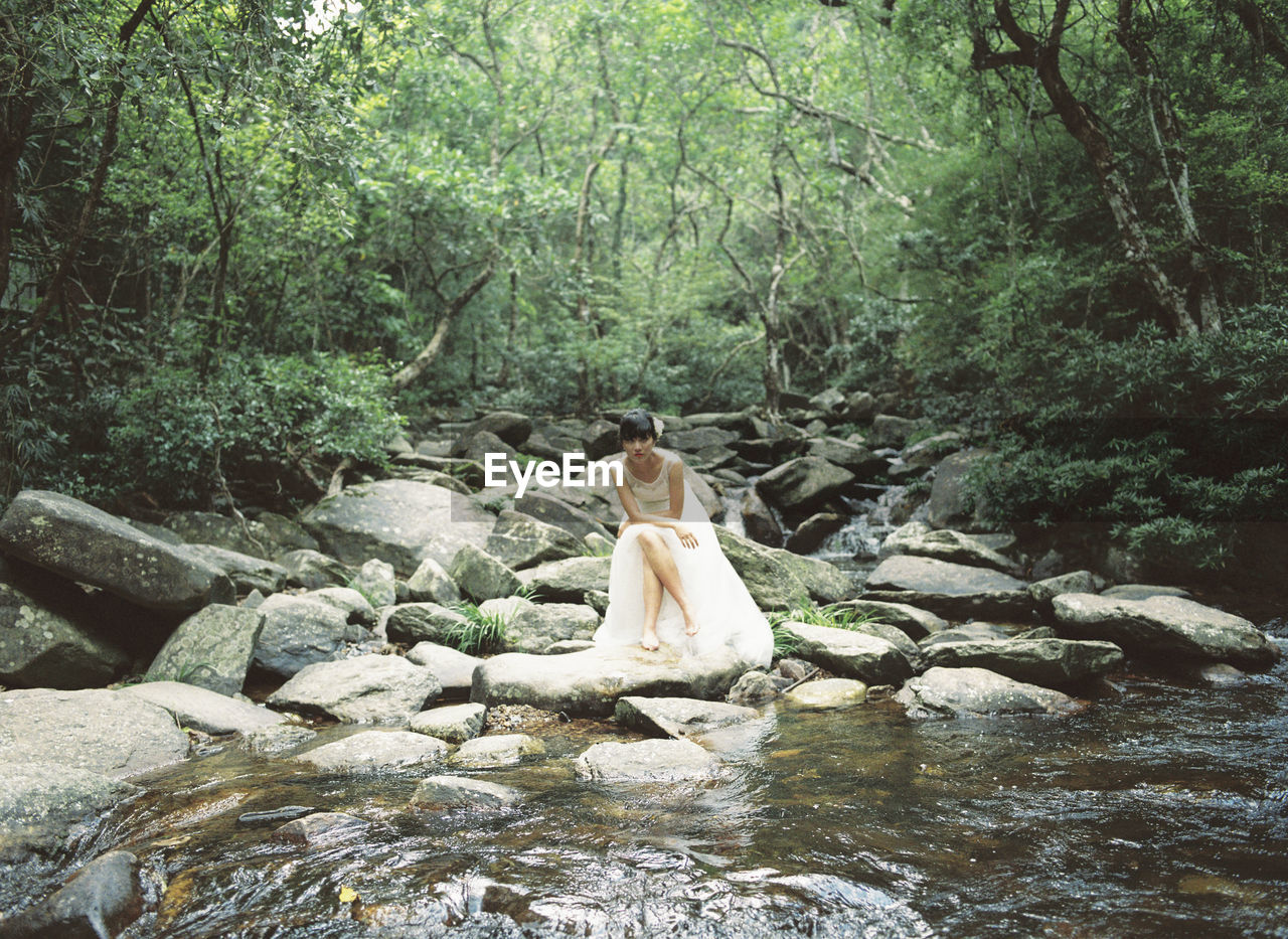 Woman sitting on rock by stream in forest