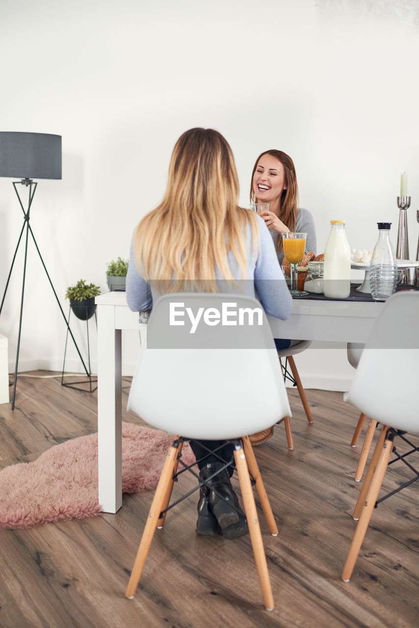 WOMAN SITTING ON TABLE WHILE LOOKING AWAY AT HOME