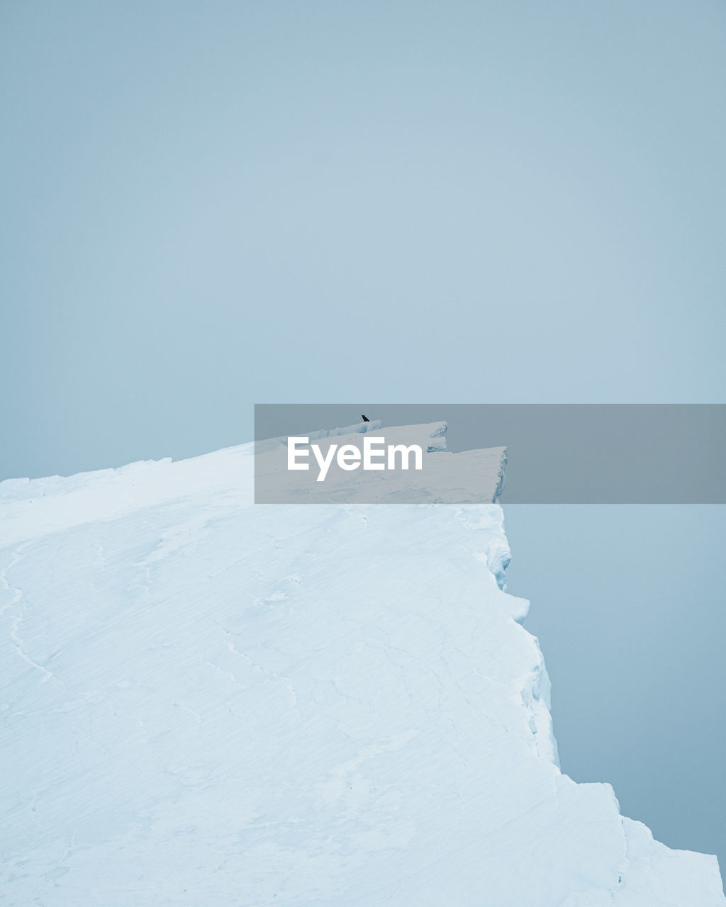 Cliff of snow covered land against clear sky