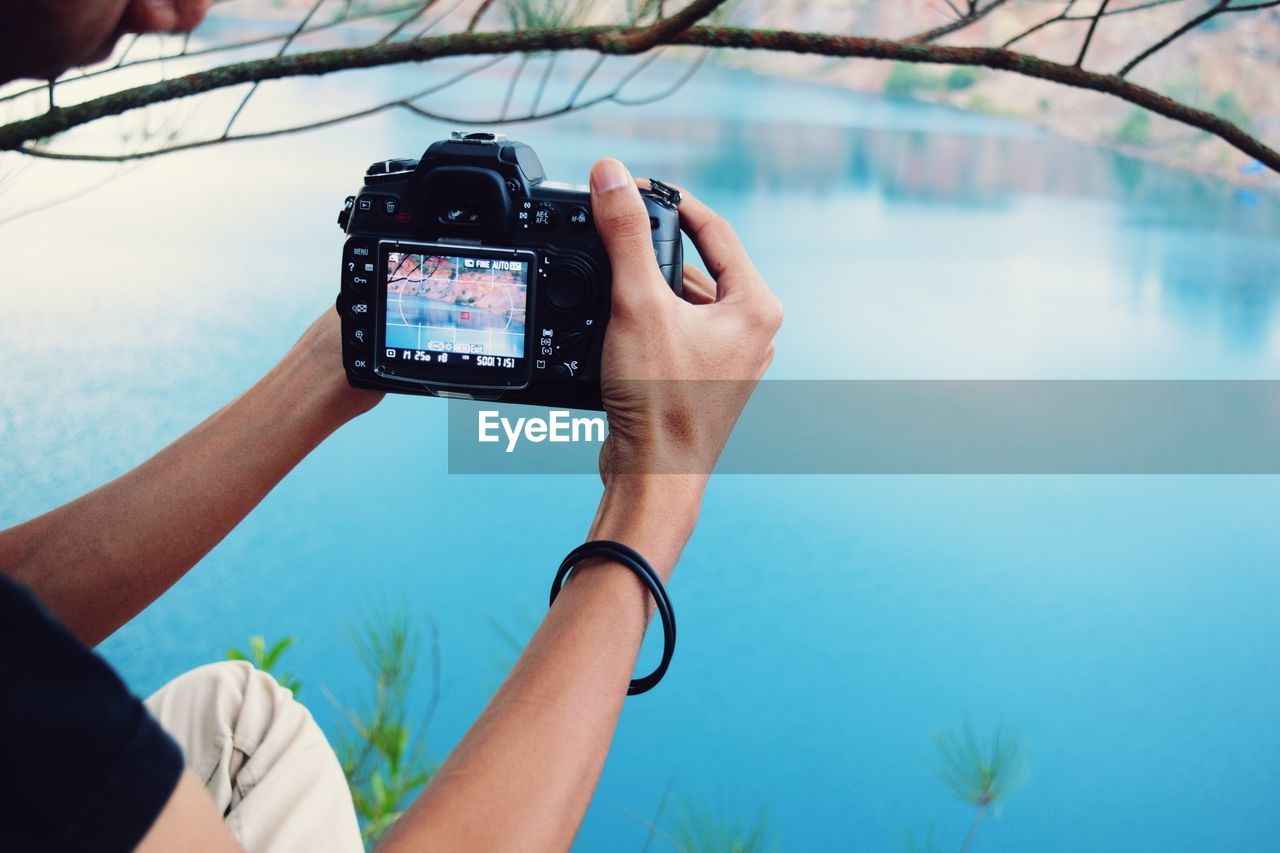 photography themes, water, technology, real people, one person, leisure activity, human hand, photographing, holding, lifestyles, nature, focus on foreground, hand, activity, day, wireless technology, camera - photographic equipment, outdoors, digital camera, swimming pool
