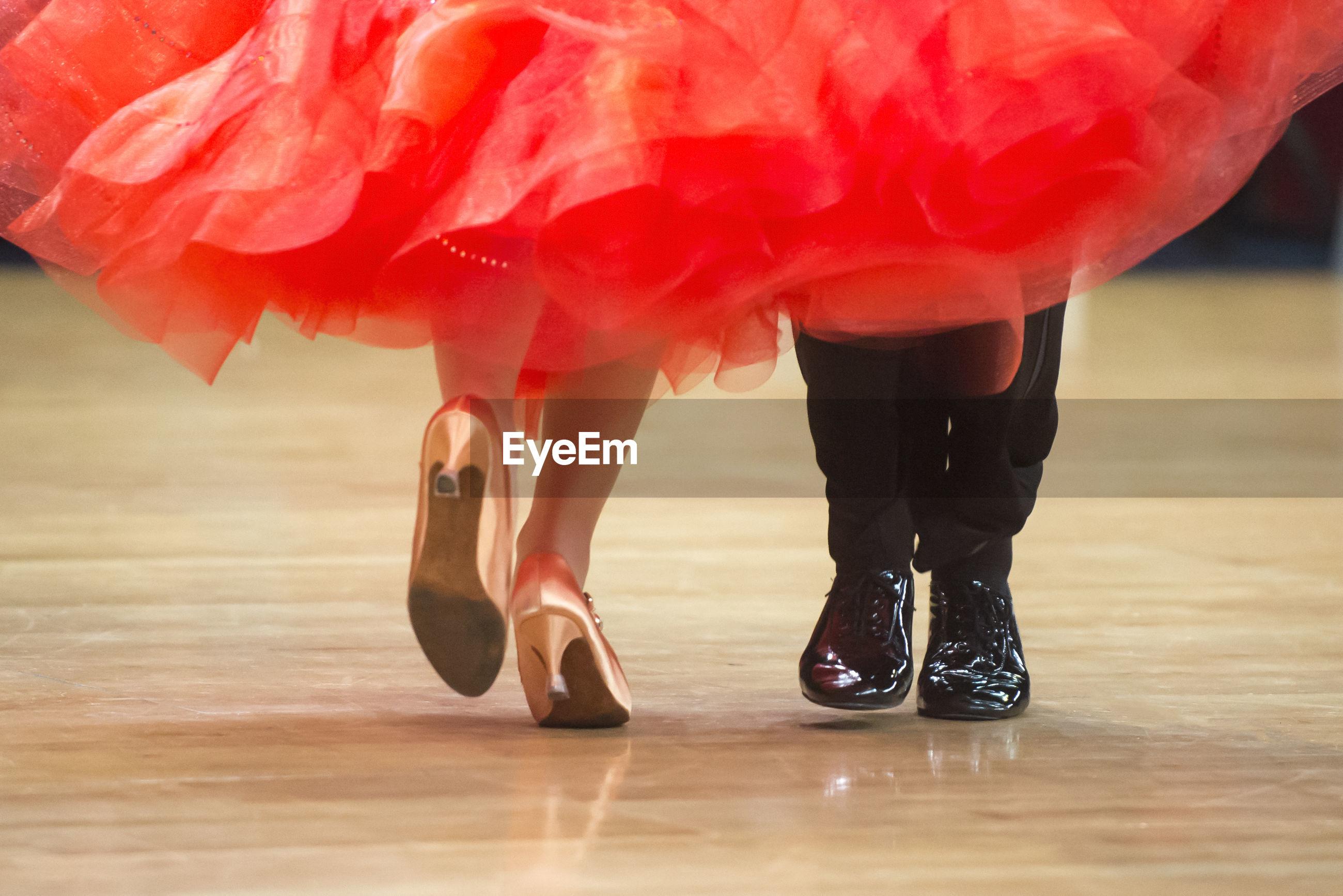 Low section of couple dancing on hardwood floor