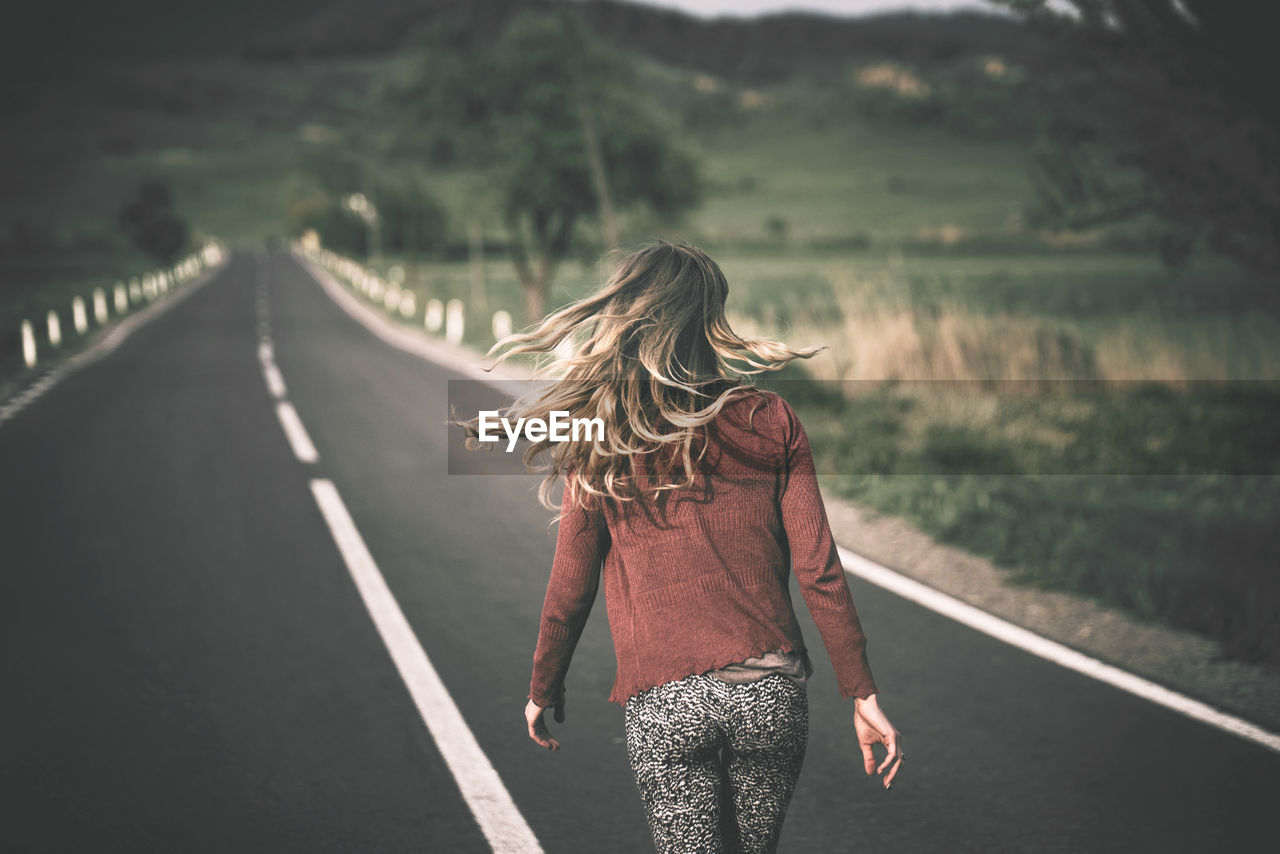 Rear View Of Woman Walking On Road During Sunny Day
