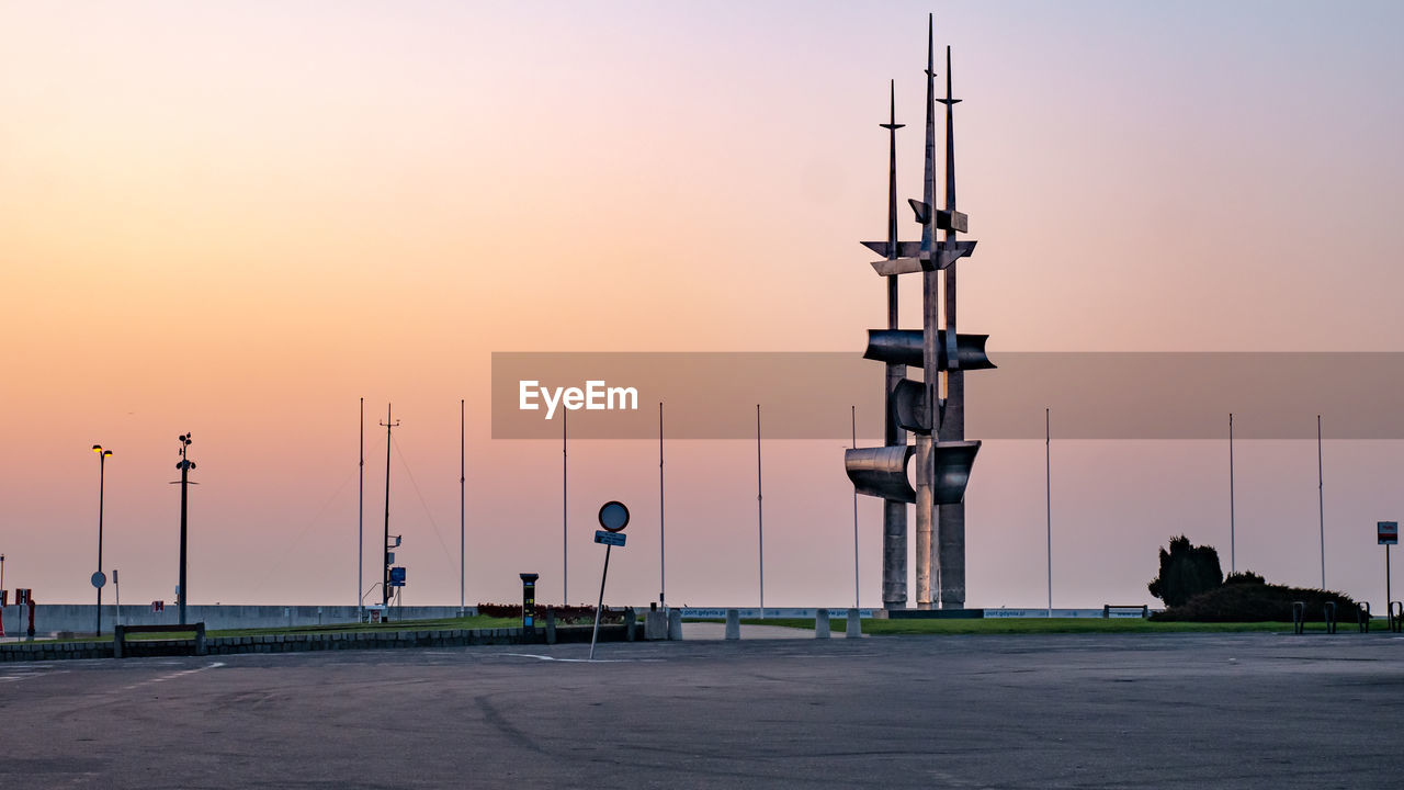 sky, sunset, orange color, architecture, technology, built structure, communication, street, lighting equipment, street light, no people, nature, transportation, tower, tall - high, outdoors, road, clear sky, connection, electrical equipment