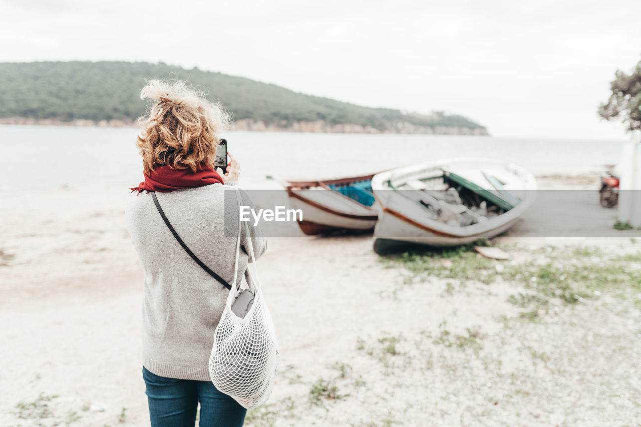 REAR VIEW OF WOMAN STANDING ON SHORE