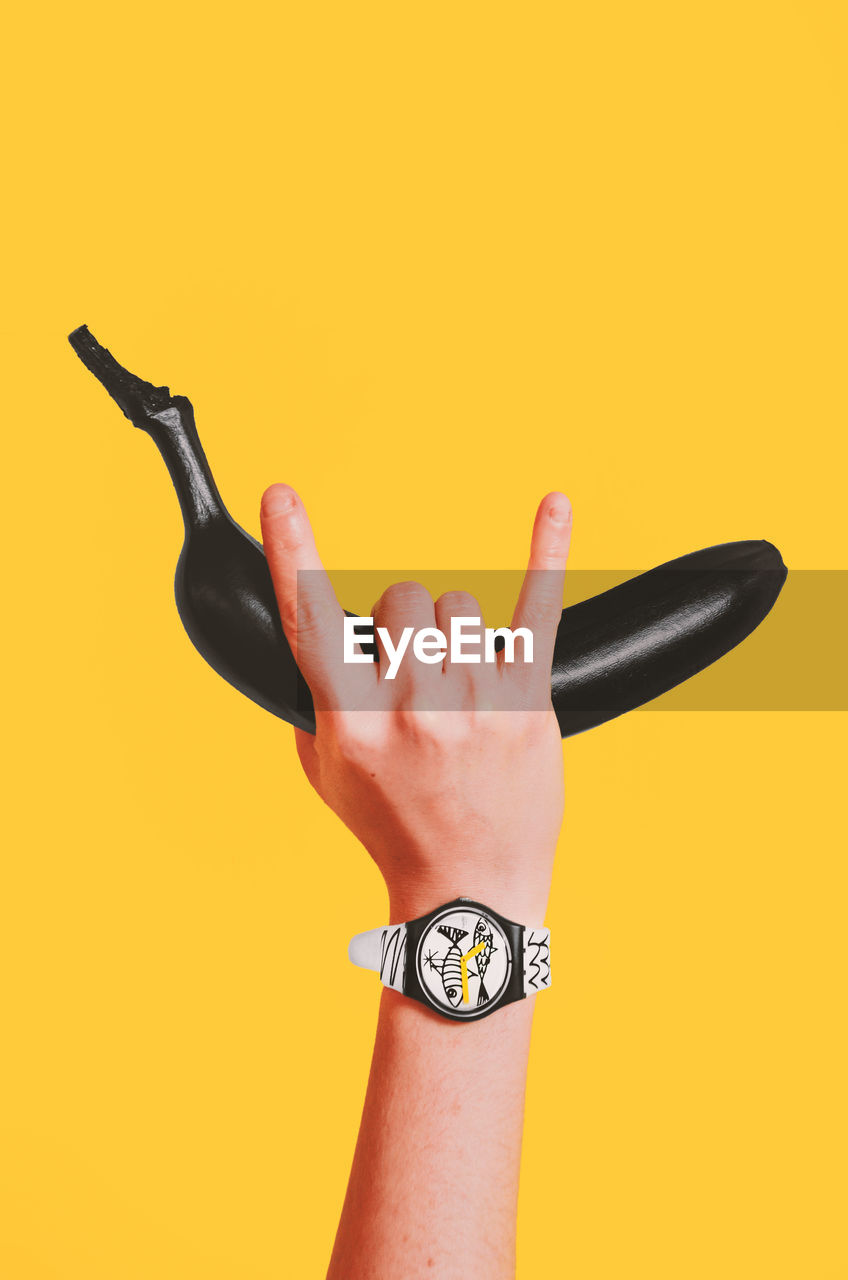 yellow, hand, human hand, one person, studio shot, human body part, indoors, yellow background, colored background, watch, wristwatch, body part, copy space, time, lifestyles, real people, human finger, finger, cut out