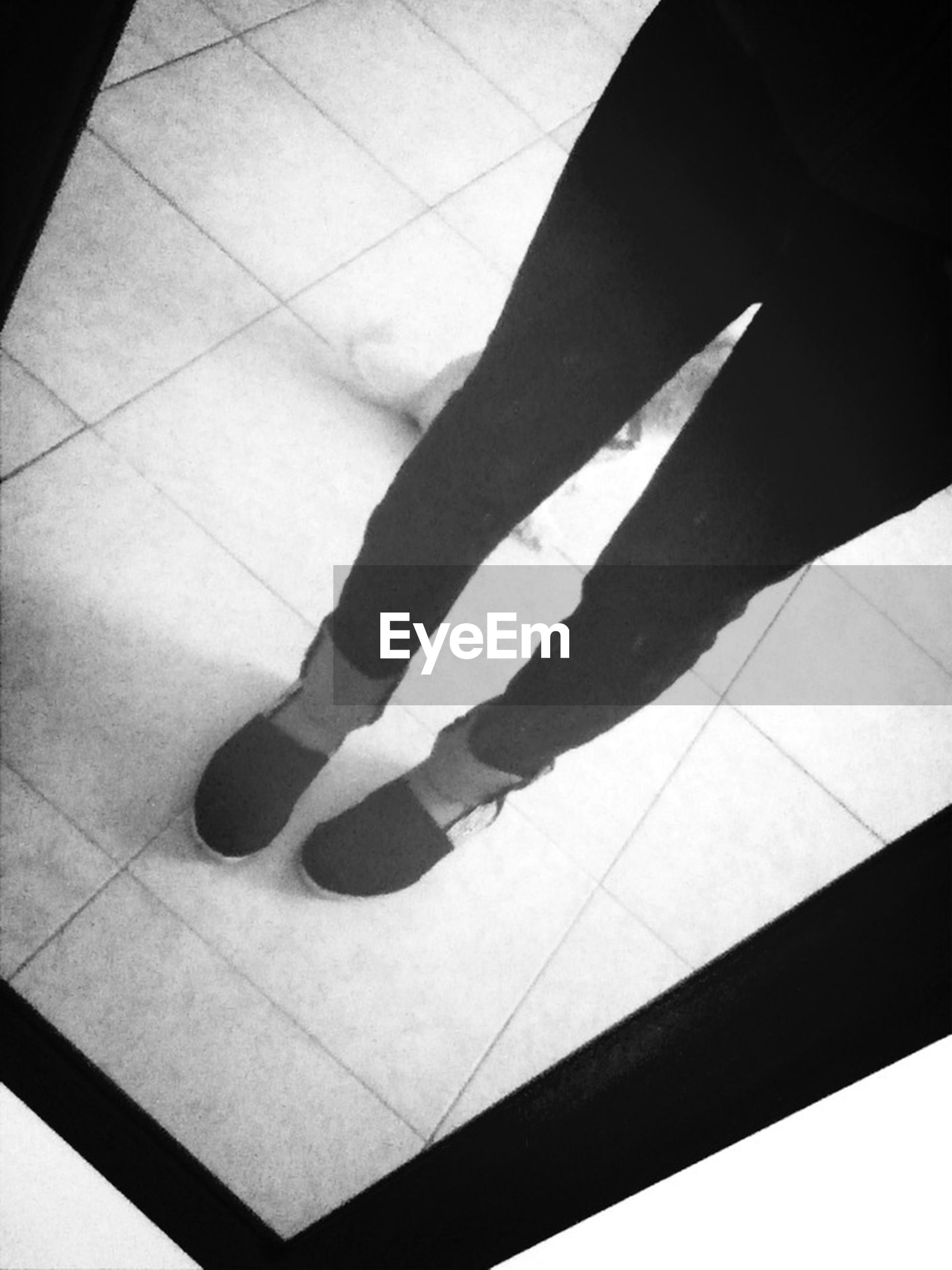 high angle view, indoors, low section, person, shadow, flooring, lifestyles, pattern, tiled floor, shoe, human foot, leisure activity, standing, footwear, unrecognizable person, floor