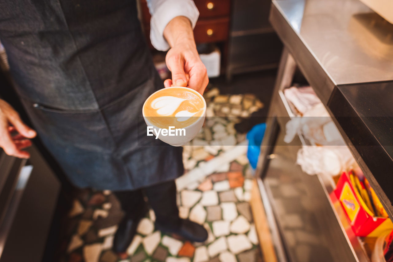 Close-Up Of Barista Holding Coffee Cup At Cafe